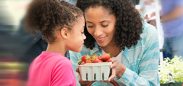 Woman and her daughter examine strawberries