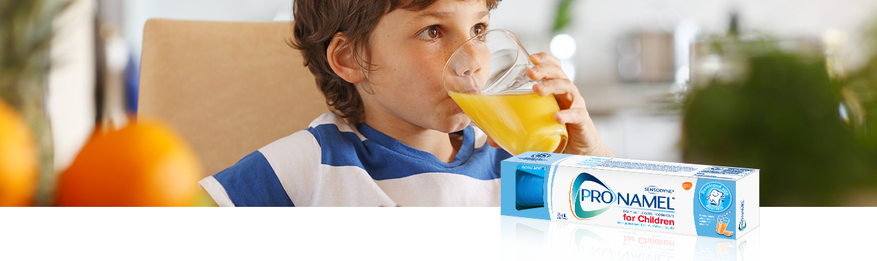 Small boy drinking acidic orange juice from a round glass