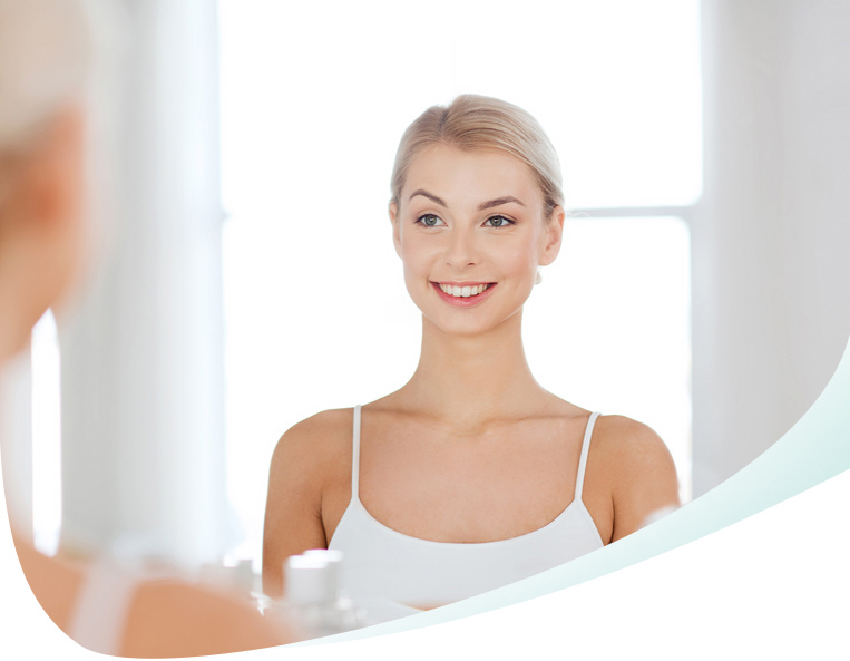 Young woman smiles and stands in front of the mirror
