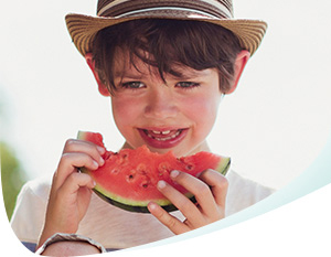 Boy in a hat eating acidic watermelon