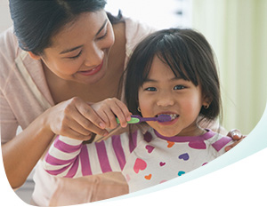 Mom helps her daughter brush her teeth with Pronamel®