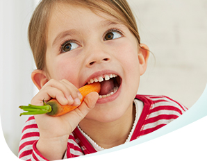 Young girl biting into a carrot